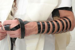 Jewish Man wrapped in tefillin pray . A religious orthodox Jew with arm-tefillin on his left hand prays Stock Images