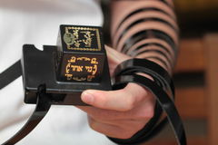 Jewish Man wrapped in tefillin pray . A religious orthodox Jew with arm-tefillin on his left hand prays. Pair of tefilin and Tallit A symbol of the Jewish people Stock Photography