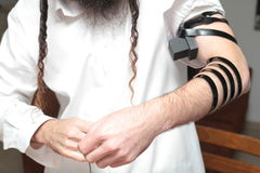 Jewish Man wrapped in tefillin pray . A religious orthodox Jew with arm-tefillin on his left hand prays. Pair of tefilin and Tallit A symbol of the Jewish people Royalty Free Stock Photos