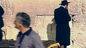 Jewish men praying. Jerusalem, Israel - Circa 1981: Jewish men in typical black dress and hat praying at Western Wall in Old City of Jerusalem. Historic footage stock footage