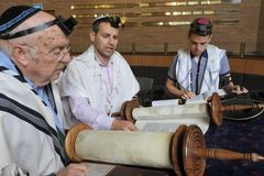 Jewish men reading and praying from a Torah scroll royalty free stock images