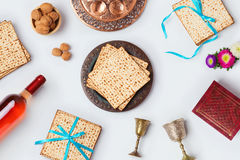 Jewish Passover holiday Pesah celebration concept with matzoh, wine and seder plate over white background. View from above. Flat l royalty free stock photo