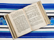 Jewish Prayer Book, Siddur, Prayer Shawl, Tallit. A Jewish prayer book, or Siddur, open and on top of a Jewish prayer shawl, or Tallit Stock Photos