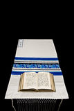 Jewish Prayer Shawl, Tallit. A Jewish prayer book, or Siddur, on a prayer shawl, or tallit, against a black background with room for text Stock Images