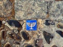 Jewish Quarter, Toledo, Spain. Jewish 7 seven arm menorah on tile on cobble stone pavement, Jewish Quarter, Toledo, Castile La Mancha, Spain Royalty Free Stock Images