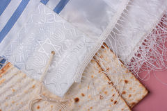 Jewish symbols. Two pieces of matzah laying next to a blue and white tallit Royalty Free Stock Image