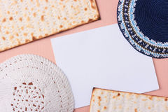 Jewish symbols. Blue and white kippahs laying next to matzah and a white piece of paper. Add your text to the paper Royalty Free Stock Images