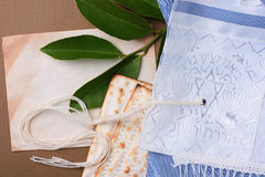 Jewish symbols. Matzah and a blue and white tallit laying next to an old piece of paper Stock Photography