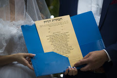 Jewish wedding, a  contract, close-up. Wedding rings and Ketubah - a prenuptial agreement in the Jewish religious tradition Royalty Free Stock Photos