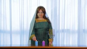 A Jewish woman in a cape lights candles in honor of the arrival of Shabbat. stock video footage