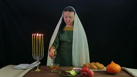A Jewish woman dips a date in honey in honor of Rosh Hashanah and tries. Overall plan stock video footage