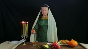 A Jewish woman dips a date in honey in honor of Rosh Hashanah and tries. Overall plan stock video