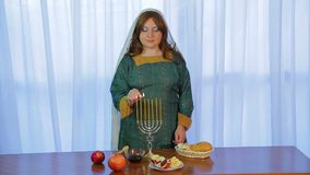 A Jewish woman lights candles in a beautiful candlestick on Rosh Hashanah at the festive party with treats stock footage