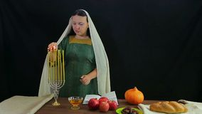 A Jewish woman lights candles in a festive candlestick in honor of Rosh Hashanah. stock video