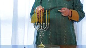 Jewish woman lights menorah on the eve of the holiday stock footage
