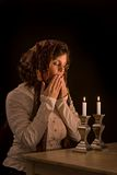 Jewish Woman Prays Over Sabbath Candles. Jewish woman says the blessing upon lighting the sabbath candles and kisses fingertips in the traditional way Stock Photos