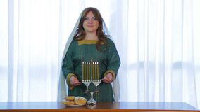 A Jewish woman stands at Hanukkah with candles burning smiling stock video
