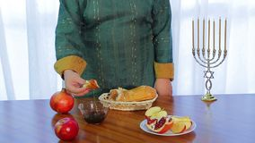 A Jewish woman takes a piece of challah and dips it in honey for Rosh Hashanah stock video footage