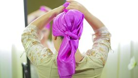 Jewish woman ties a festive scarf in front of a mirror. Back view stock video