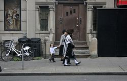 Jews in Brooklyn, New York. New York, United States - 3 September 2016 - Family walking along the street in Jewish neighbourhood in Brooklyn, dressed in Jewish royalty free stock image