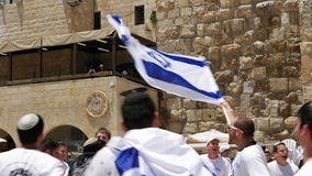 Jews dancing in a round with flag in Jerusalem. Jerusalem, Israel - May 25, 2017: Jews dancing in a round with flag celebrating the Jerusalem Day at Western Wall stock video footage