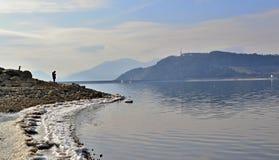 Jeziorny brzeg z paskiem śnieg i trwanie osobą na kamieniu Zdjęcia Royalty Free
