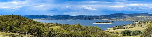 Jeziorny Jindabyne krajobraz z chmurzącym niebem i wiejskim przedpolem Fotografia Stock