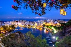 Jeziorny Voulismeni w Agios Nikolaos przy nocą z fullmoon, malowniczy miasteczko przybrzeżne z kolorowymi budynkami wokoło portu Zdjęcia Stock
