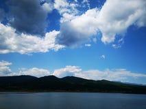 Jezioro otaczający górami i chmurami fotografia stock