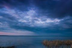 Jezioro pod burzowym niebem spokojna woda, zmrok wałkoni się heban zdjęcia royalty free