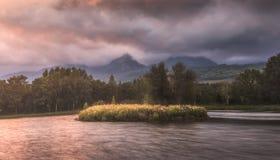Jezioro pod szczytami góry przy zmierzchem zdjęcie royalty free