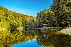 Jezioro w lesie z gazebo i mały molo dla przyjemność następu catamaran na jeziornym brzeg Zdjęcia Royalty Free
