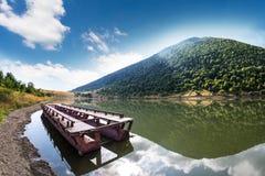 Jezioro z łodzią przy górami Fotografia Royalty Free