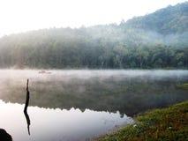Jezioro z małą łódką przy ranek mgłą Zdjęcie Royalty Free