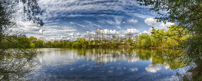 Jezioro z odbicie chmurami i drzewami Zdjęcia Royalty Free