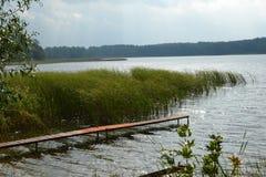 Jezioro z popple wodą i małym mostem zdjęcie royalty free