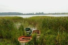 Jezioro z trzy łodzią na brzeg i sitowiu obrazy royalty free
