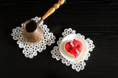 Jezva mit Kaffee, Untertasse mit rotem Herz-förmigem Lebkuchen auf einem schwarzen hölzernen Hintergrund Stockfotos