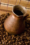 Jezve avec du café entouré par des grains de café Images stock