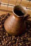 Jezve met koffie die door koffiebonen wordt omringd Stock Afbeeldingen