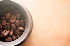Jezve mit Kaffeebohnen auf hölzernem Hintergrund Stockfotografie