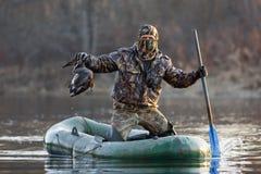 Jäger mit einer Ente in einem Boot Lizenzfreie Stockbilder