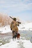 Jäger mit seinem Jagdhund während einer Winterjagd Lizenzfreies Stockfoto