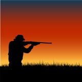 Jägerschattenbild am Sonnenuntergang Lizenzfreie Stockfotografie