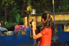 Jhargram västra Bengal, Indien Oktober 17,2018: En tonårs- flicka som försöker att fånga fotografiet med kameran royaltyfri bild