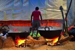 Jhargram, West-Bengalen, India - December 15,2018: Sommige mensen koken voedsel in een grote Steelpan voor het vieren van het huw royalty-vrije stock fotografie