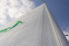 Jib. View along the jib of a sailing yacht towards the top of the mast. The green tell-tale stands out against the white sail Stock Photography