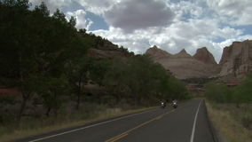 Jib shot of three motorcycles passing camera in capitol reef national park. Video of jib shot of three motorcycles passing camera in capitol reef national park stock footage
