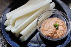 Jicama-Stock und Tomate Tahini tauchen auf eine Platte ein Stockfotos