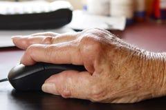 Jichtige hand die een muis met behulp van Stock Fotografie